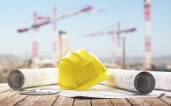 Elmetto giallo con progetto cantieri gru